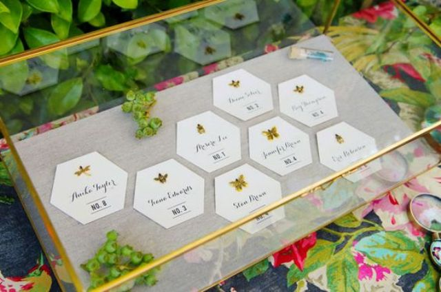paper honeycomb seating cards decorated with gold insects