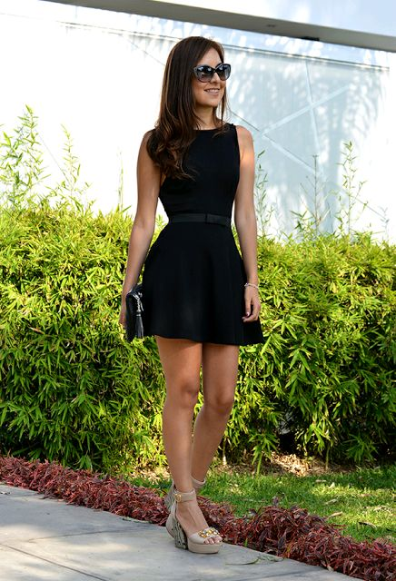 sleeveless halter neckline black mini dress with a black clutch is classics