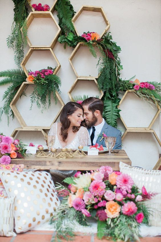 hexagon sweetheart table backdrop with lush greenery and bold blooms