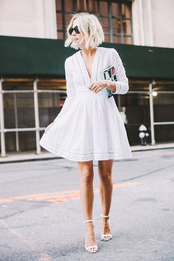 white perforated mini dress with a V-neckline and ankle strap heels
