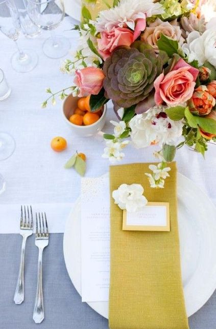 a neutral tablescape with a bold floral centerpiece and a mustard napkin