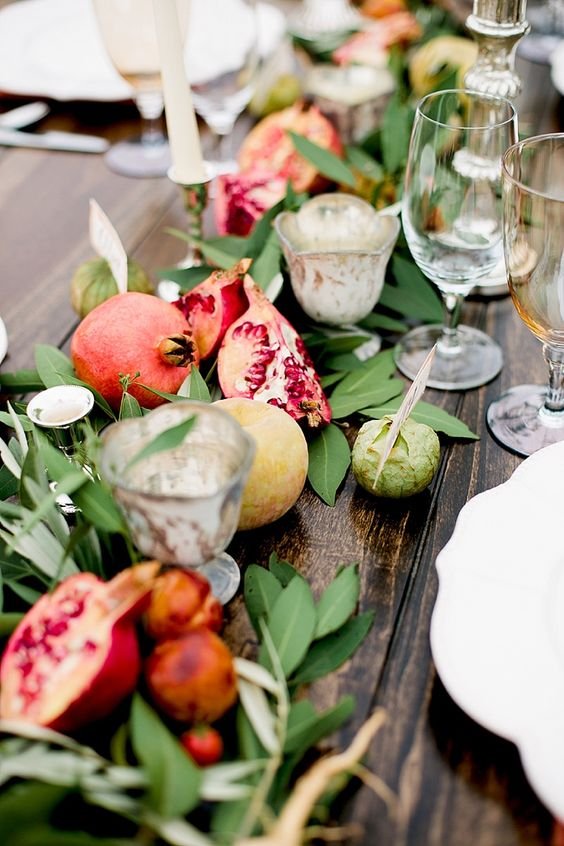 a greenery, apple and pomegranate table runner with candles incorporated