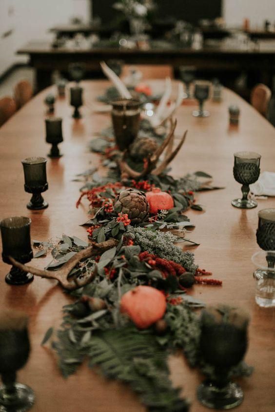 a moody greenery table runner with berries, pomegranates, antlers and artichokes