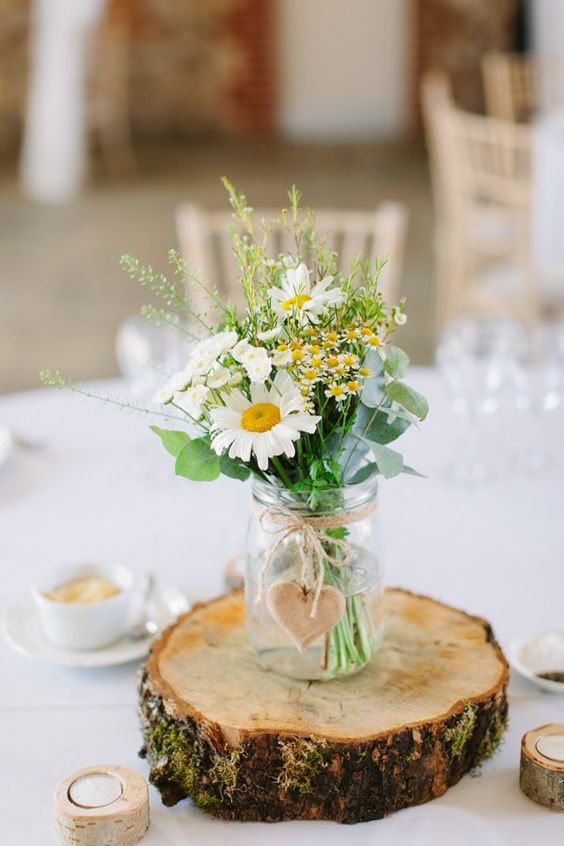 a wood slice with a jar, a wooden heart and wildflowers will be great for a summer wedding