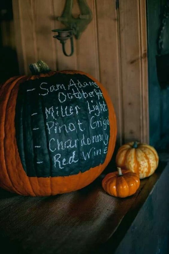 a large orange pumpkin covered with chalkboard paint and used for displaying a menu