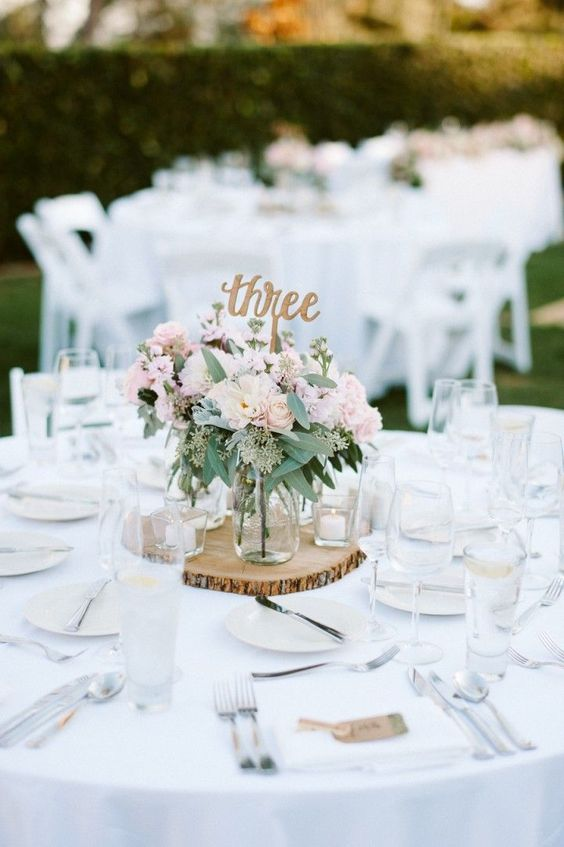 a simple white table setting with a wooden slice and cadles and a pink floral centerpiece is easy to recreate