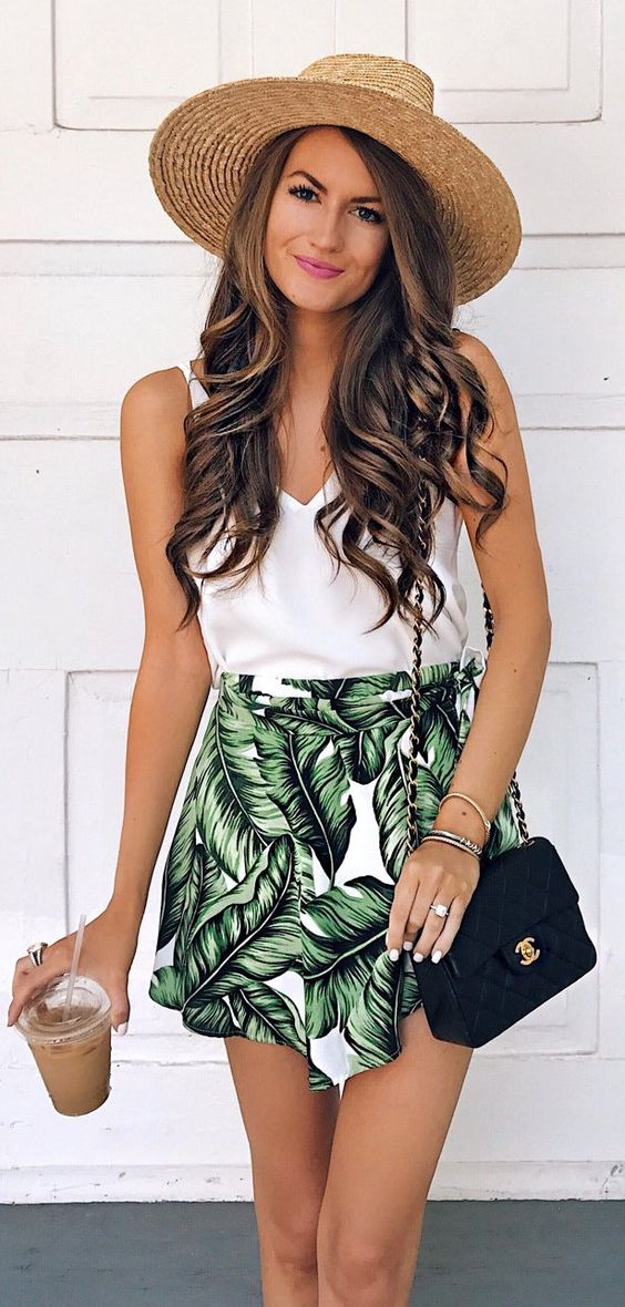 a simple white top and a tropical leaf print mini skirt, a black crossbody