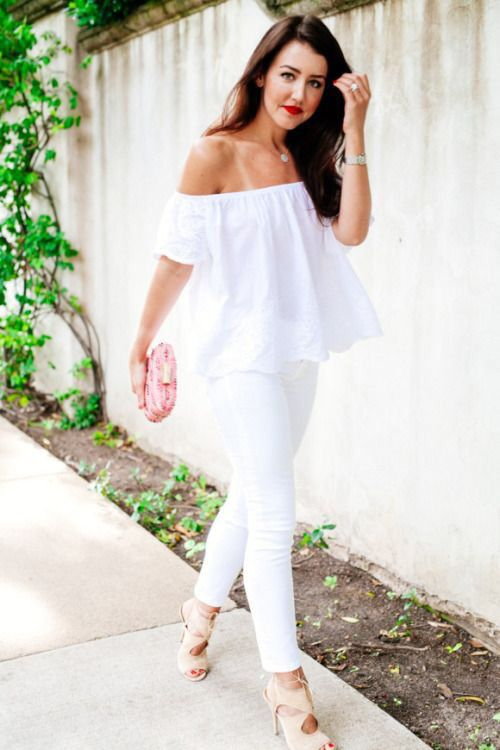 white jeans, an off the shoulder top, a pink clutch and neutral cutout shoes
