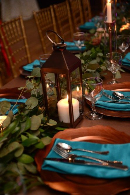 a wedding tablescape with eucalyptus, candle lanterns, copper chargers and teal napkins is pure elegance