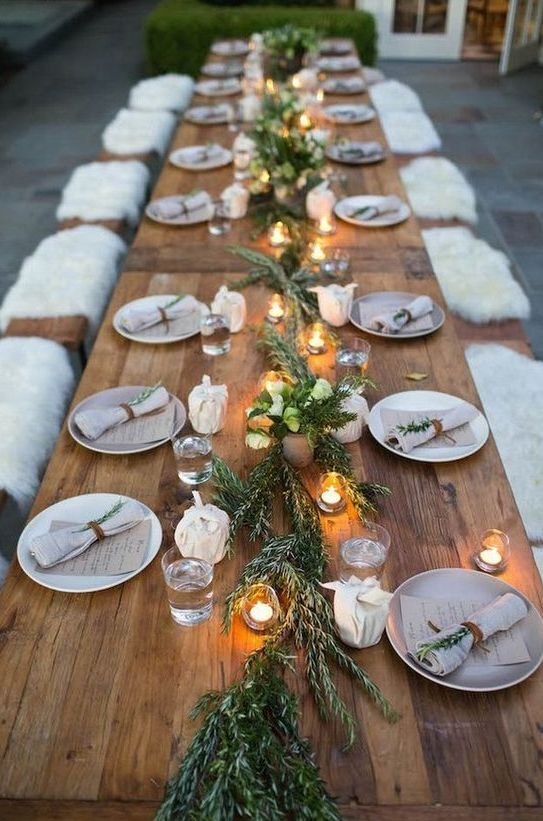 a cozy rustic tablescape with a greenery runner, candles and napkins accessorized with greenery and leather