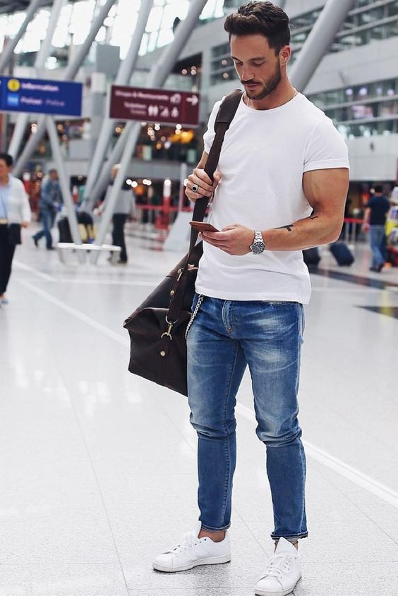 a white tee, blue jeans and white sneakers for a comfy and stylish airport look