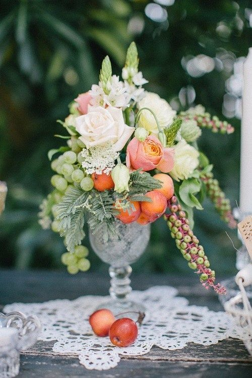 a crystal vase with white and peachy roses, green grapes and fruits for a relaxed summer wedding