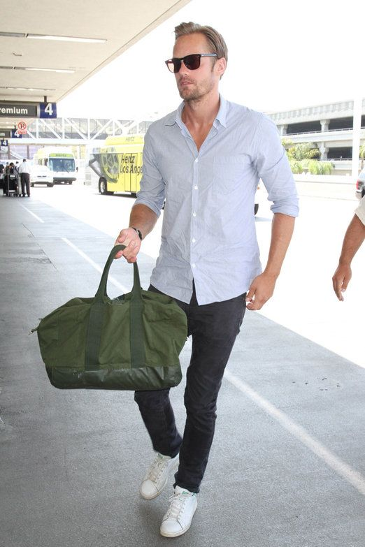 black jeans, a light blue shirt, white sneakers and a green handbag