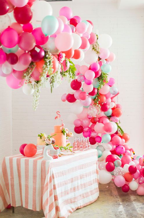 colorful balloon and tropical leaf arch over a dessert table
