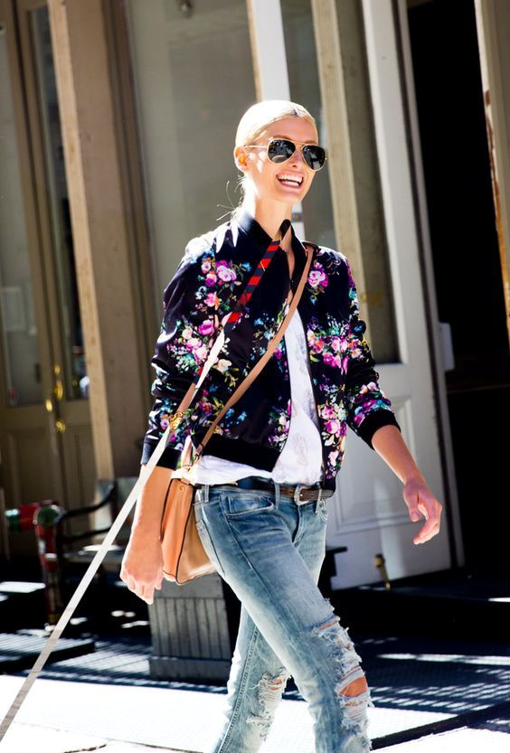 distressed jeans, a white shirt, a black floral print bomber jacket and a crossbody
