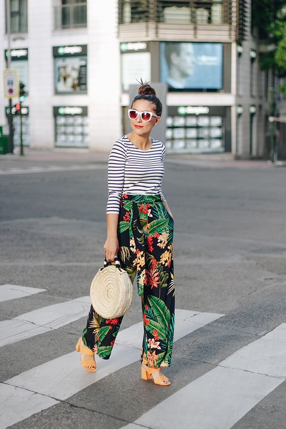 a striped blue and white long-sleeve and tropical print pants, nude heels and a straw round bag