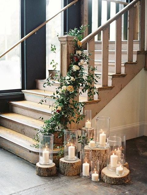 tree stumps with candles and a greenery and orange rose garland that interweaves the stairs
