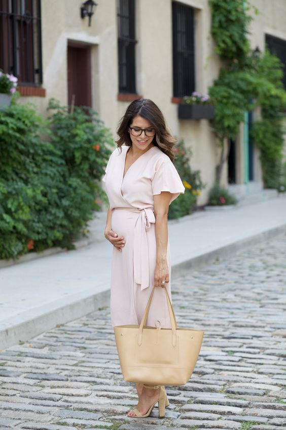 a blush wrap dress with short sleeves, nude shoes and a nude tote