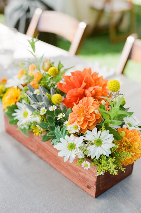 a rustic wedding centerpiece in a box with white, orange and yellow flowers