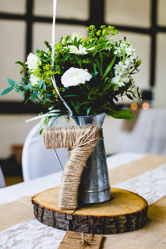 a tin pitcher with greenery and white blooms, a jute covered table number on a wooden slice
