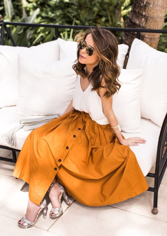a mustard midi skirt with a button row, snake print shoes and a white top