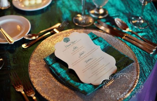 copper flatware and chargers, shiny teal npakins and a tablecloth for an exquisite look