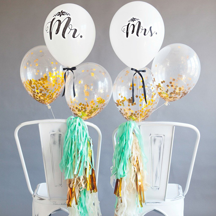 white and sheer balloons with gold confetti inside for wedding chairs decor