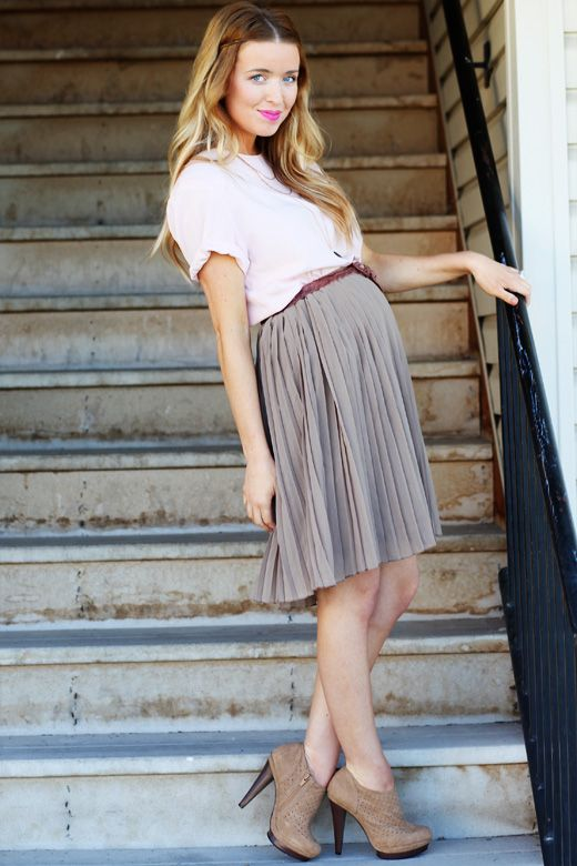a grey pleated knee skirt, a black shirt and brown booties