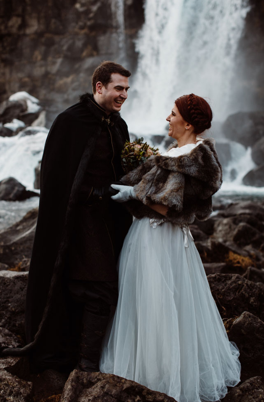The groom was dressed up in a cape, and the bride was wearing a fur coat for the outside ceremony