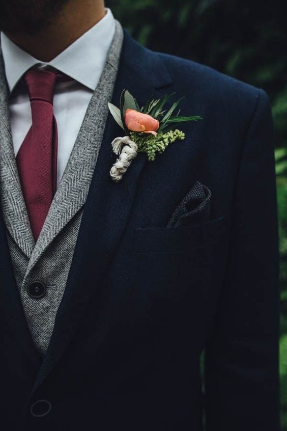a navy suit, a grey waistcoat, a neutral shirt and a maroon tie