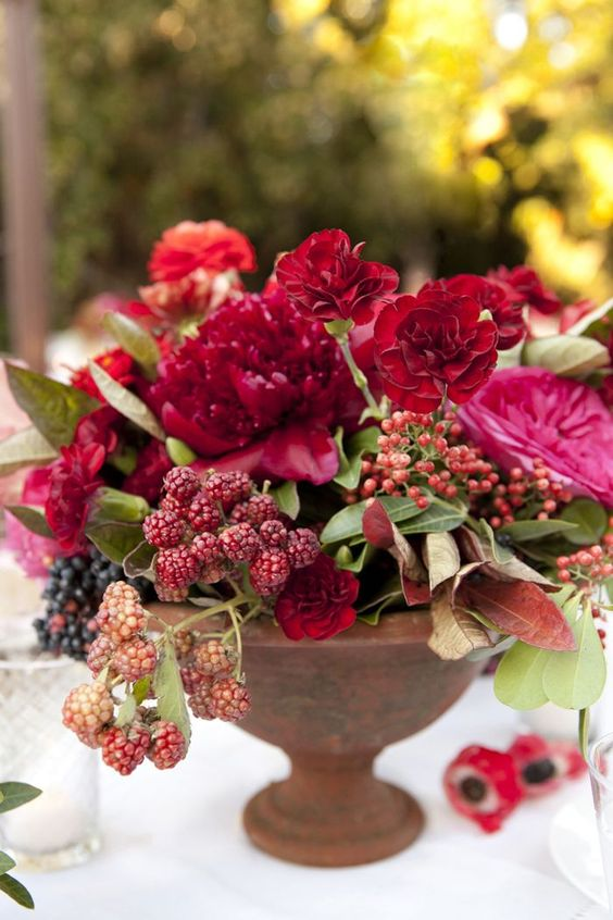 a bold summer arrangement with ruby red blooms and raspberries for a summer celebration