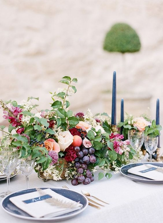 a beautiful centerpiece with blush and burgundy blooms, leaves and grapes in a gold bowl