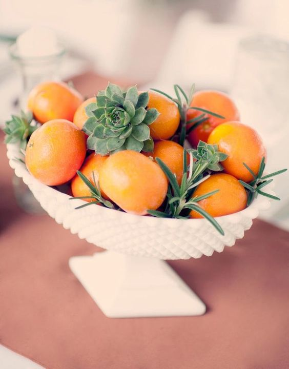 a white bowl with tangerins, succulents and herbs for a summer or tropical wedding