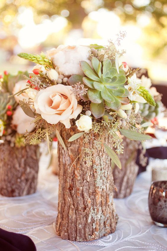 a tree stump with flowers and a succulent will be a nice centerpiece