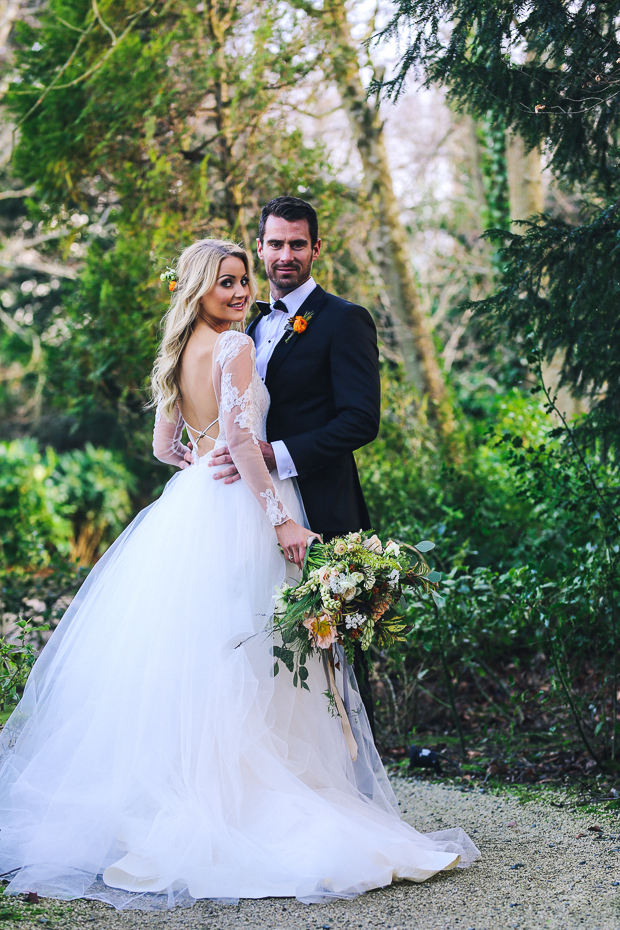 The bride in a deep back cut ballgown with illusion lace long sleeves and criss-cross straps