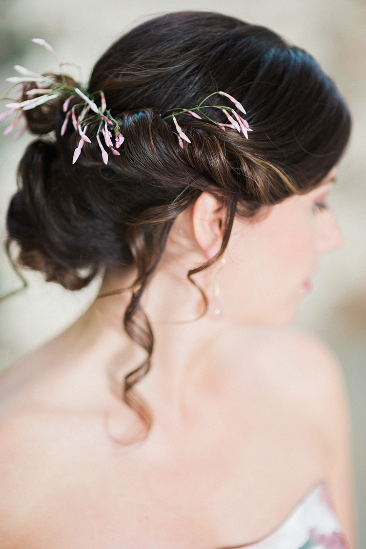 wedding updos with delicate flowers - photo by Linda Nari Photography http://ruffledblog.com/tuscan-warehouse-wedding-inspiration-with-a-floral-bridal-gown