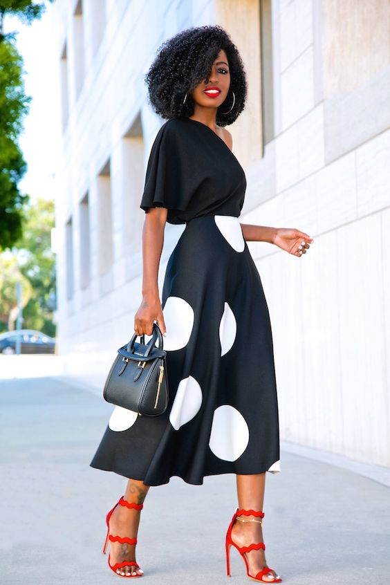 a black one shoulder top, a black and large white polka dot midi skirt and red strappy shoes