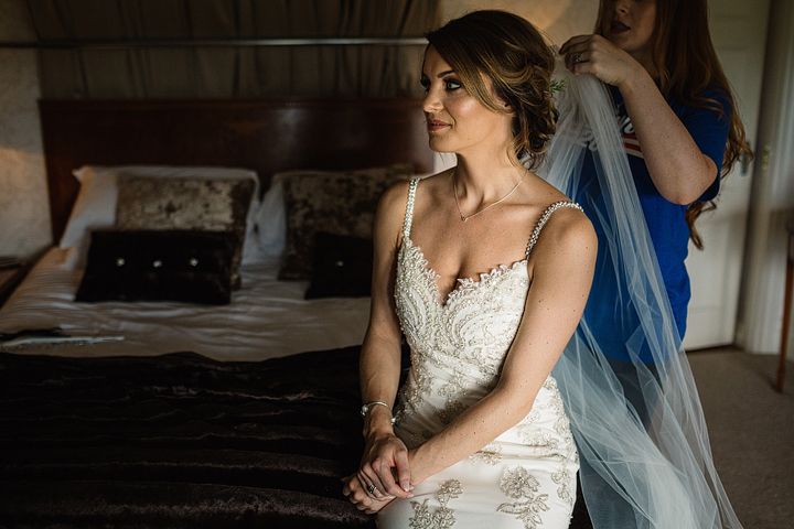 The dress was an ivory one with gold embroidery, with rhinestone spaghetti straps and a veil