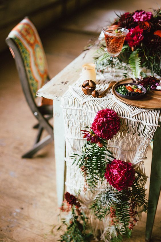 a macrame table runner with crimson blooms and greenery for a boho fall wedding