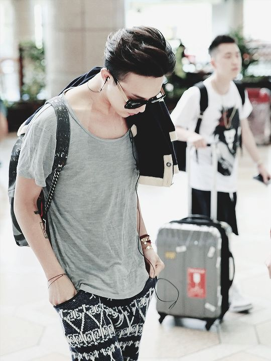 a loose grey tee, pinted black and white shorts and a backpack, relaxed rock style