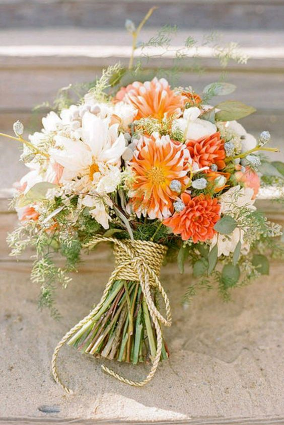 soft neutral bouquet with a couple of bold orange flowers wrapped with rope
