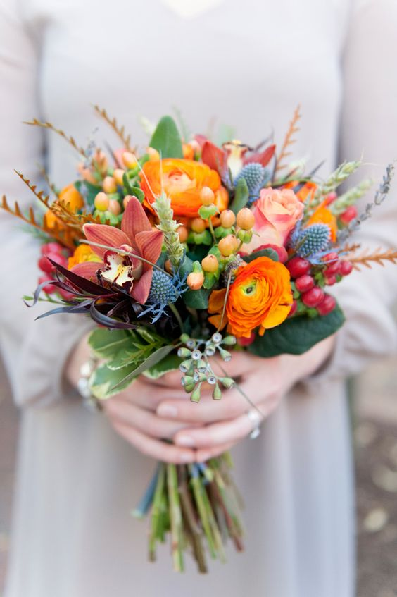 a beautiful wedding bouquet with orange and burgundy blooms and textures
