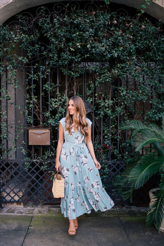 a blue maxi dress with a pink floral print, heeled sandals and a straw bag