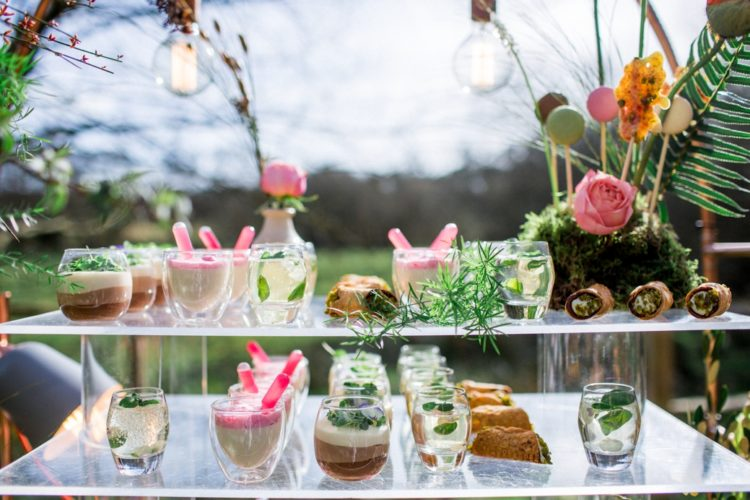 Drinks and desserts served on a glass stand and a moss stand with macaron pops become a part of decor