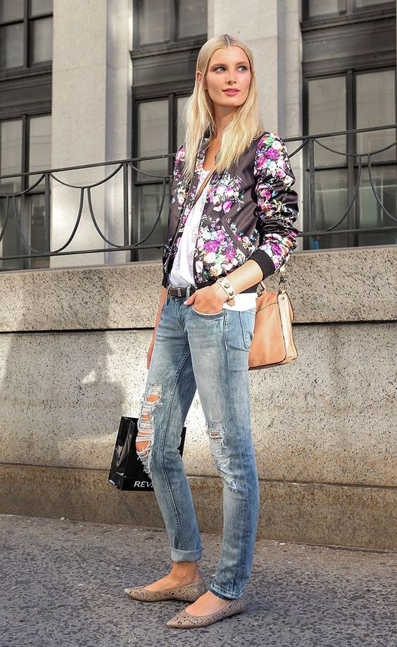distressed jeans, a white lace top, a black floral print bomber, a neutral bag and laser cut flats