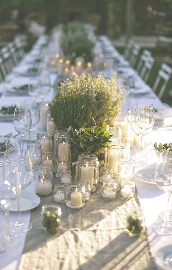 multiple jars with candles, potted herbs and greenery and a burlap runner