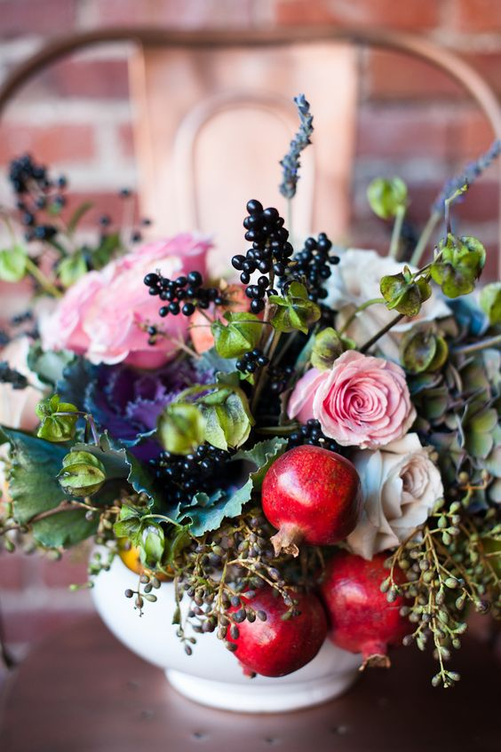 a beatiful centerpiece with pomegranates, berries, pink and white roses for a fall or late summer wedding
