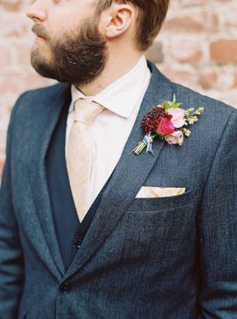 a grey tweed suit, a navy vest, a pink tie