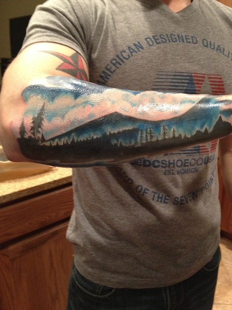Mountain with clouds and forest tattoo