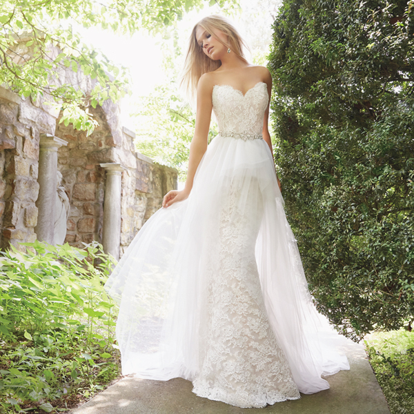 a sheath strapless sweetheart neckline wedding dress and a tulle overskirt accentuated with an embellished belt